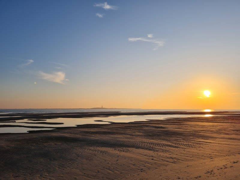 Uitzicht richting de vuurtoren van Texel vanaf het meest westelijke puntje van Waddeneiland Vlieland
